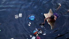 Menino que sustenta a família caçando pedaços de plástico em rio poluído